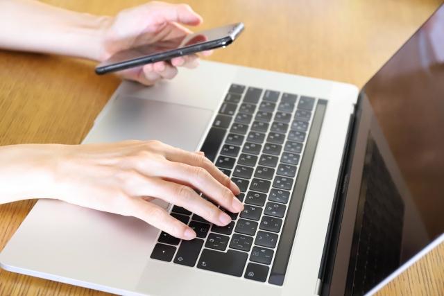 パソコンとスマートフォンを操作する男性の手